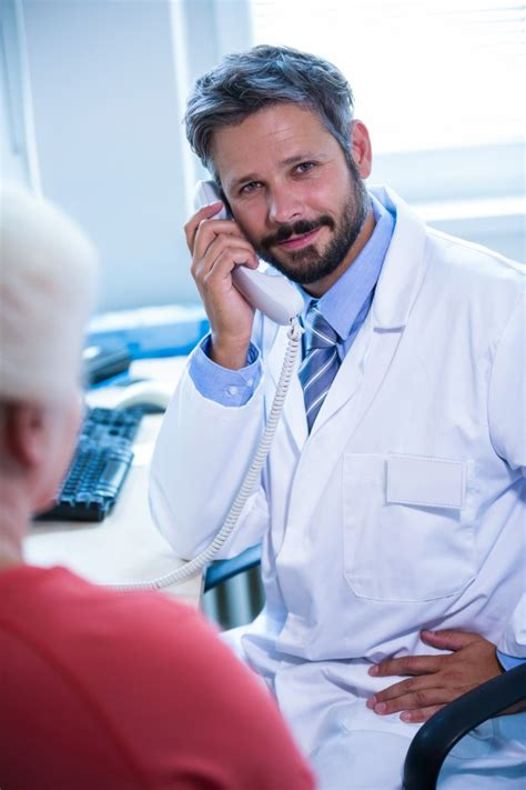the phone doctor doctor talking on landline phone in office at