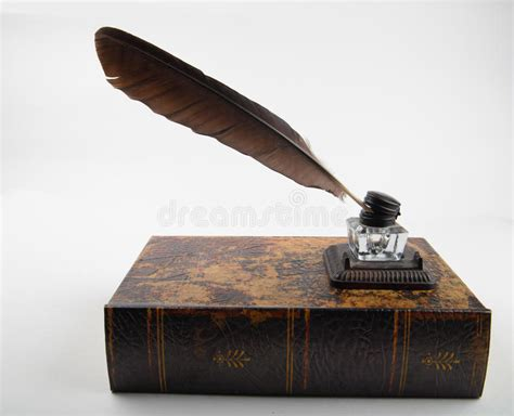 Ancient Ink Pot With Quill On Old Tome Stock Image