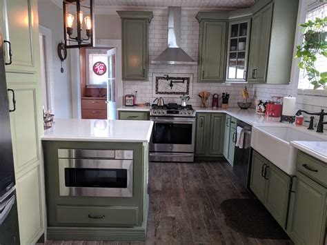 american foursquare kitchen sage green cabinets white subway tile dark grout wood tile floo