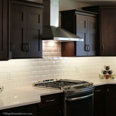 stainless steel chimney style range hood surrounded  cabinetry  highlighted  beveled