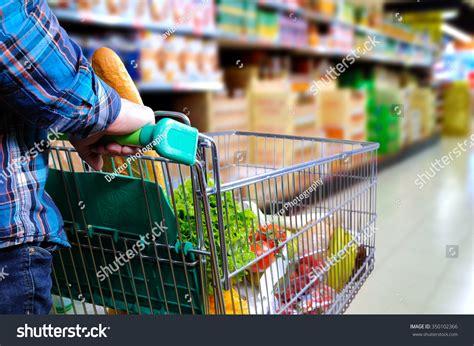 man pushing shopping cart full food stock photo