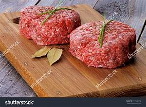 Two Fresh Raw Beef Burgers With Chives And Bay Leaf On ...