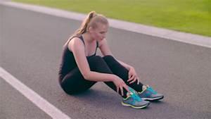 Tired runner sitting on asphalt road. Exhausted female ...