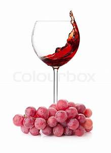 Splashing Red Wine In A Glass And Grapes Isolated On White Background