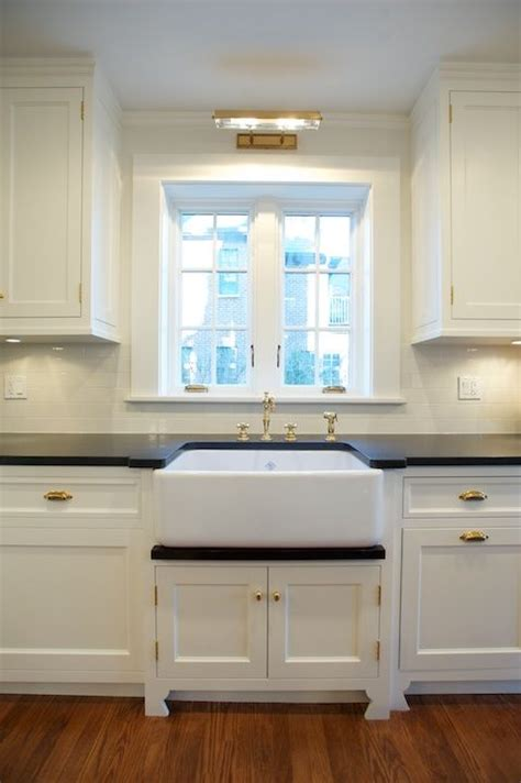 sconce over kitchen sink white kitchen cabinets with brass cup pulls design