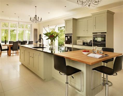 a wooden breakfast bar and granite work surfaces blend