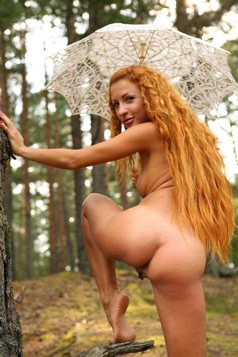 Girl With Long Red Curly Hair Posing In The Forest With