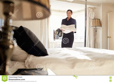 hotel femme de chambre chambermaid carrying linen in hotel bedroom low angle