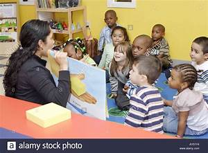 Preschool teacher reading a book to her class while the ...