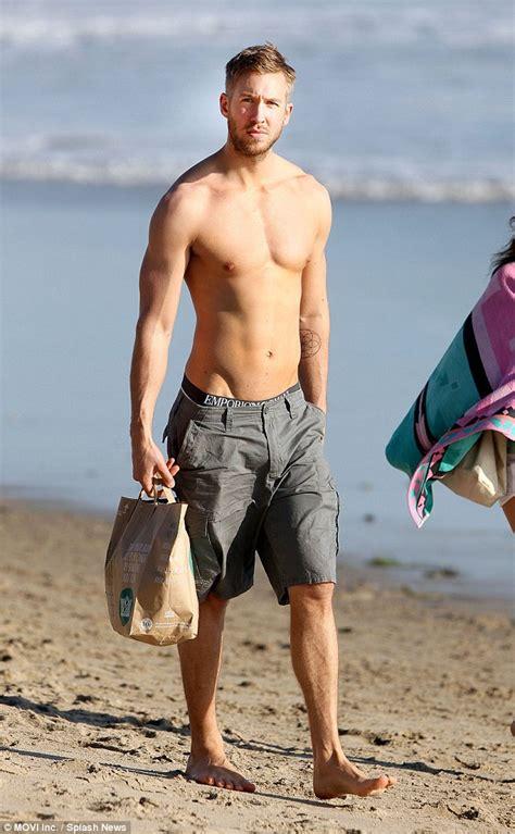 calum scott swimsuit calvin harris goes shirtless on beach with aarika wolf