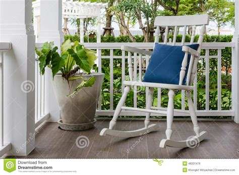 white wooden rocking chair on front porch at home stock