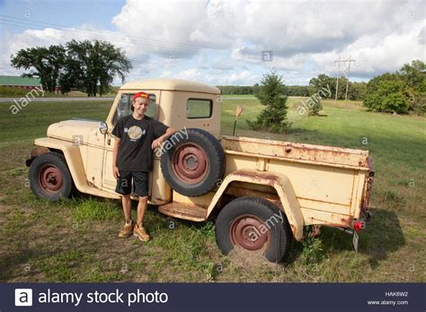 vintage willys jeep young teen standing beside old vintage willys jeep pickup