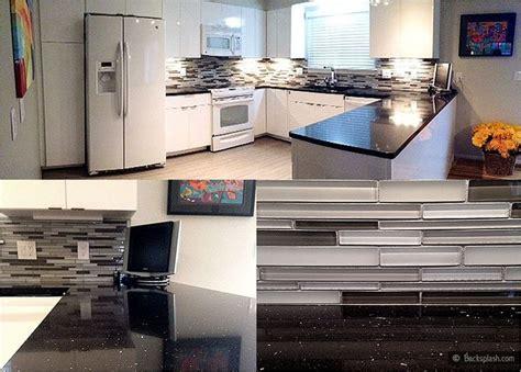 black glass backsplash white kitchen cabinets black galaxy countertop gray glass