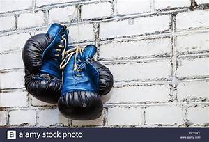 A pair of old blue and black boxing gloves hanging on ...