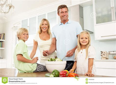 Family Preparing Salad In Modern Kitchen Stock Photography