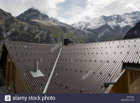 Chalet With Metal Roof And Snow Cleats With Alps Behind Metal Roofing Panels For Sale Roof Leaks Residential Cost Solar Powered Vents Contract Template Free Repair Minneapolis Frisco Sealer Home Depot