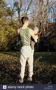Man From Behind Holding Baby Boy Stock Photo