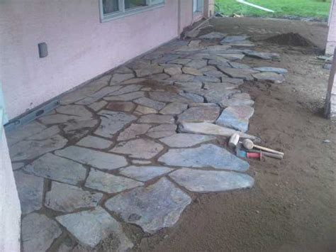 laying flagstone in sand laying and packing stones for a flagstone walkway