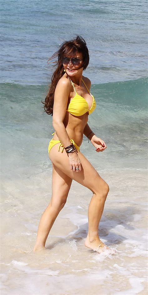 Lizzie Cundy showing off her curvy body in a yellow bikini at the beach in Barbados
