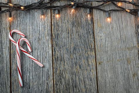 Christmas Lights And Candy Canes On Rustic Wood Background