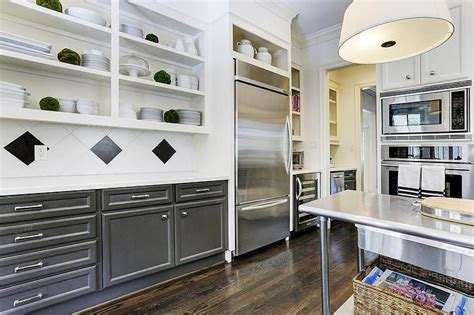 black kitchen island with stainless steel top two toned tuxedo cabinetry catching on says zillow home