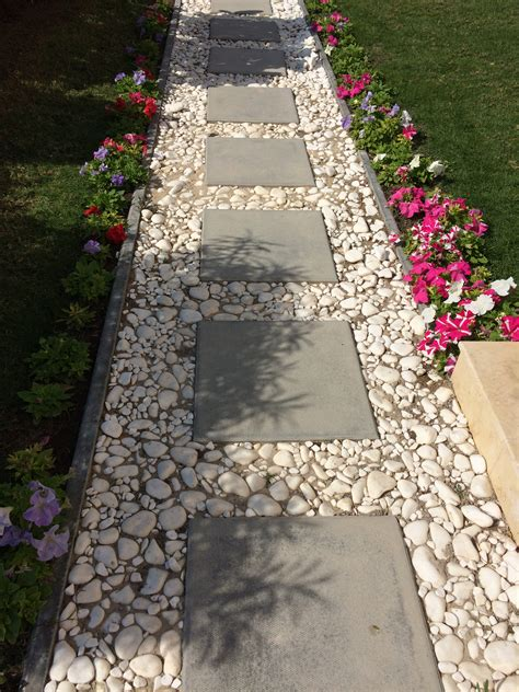 sidewalk design cement block tiles bordered by white pebbles for a simple