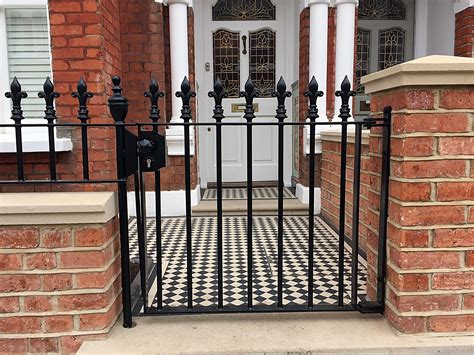 brick wall with gate red brick front garden wall heavy rails gate victrorian mosaic tile path battersea clapham