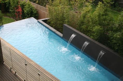 swimming pool features swimming pool with water feature wall and backdrop of