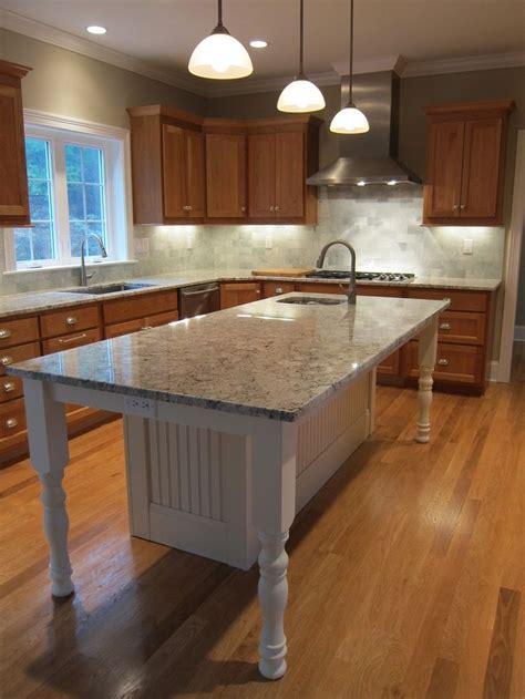 white kitchen island  granite countertop  prep sink
