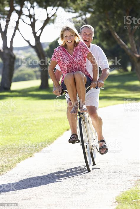 older couple riding  bike  female   handlebars