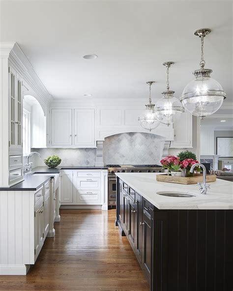 white cabinets  black island transitional kitchen