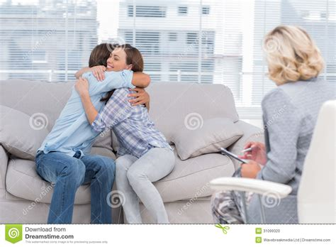 Young Couple Cuddling On The Couch Stock Photo