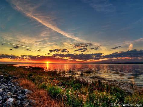 stunning sunset clouds lakeside lake shore grass nature