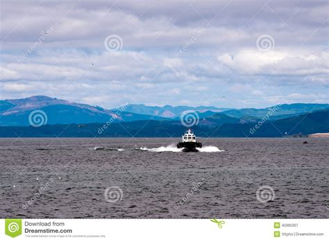 Small But Powerful Boat by Pilot Boat At The Of The Columbia River Stock Photo