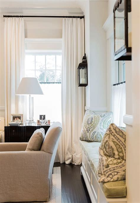 White Drapes In Living Room by Black Lantern Wall Sconces Window Upholstered Seating