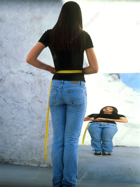 anorexic teenage girl measuring   mirror stock