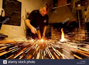 Blacksmith hammering red hot metal on an anvil with sparks ...