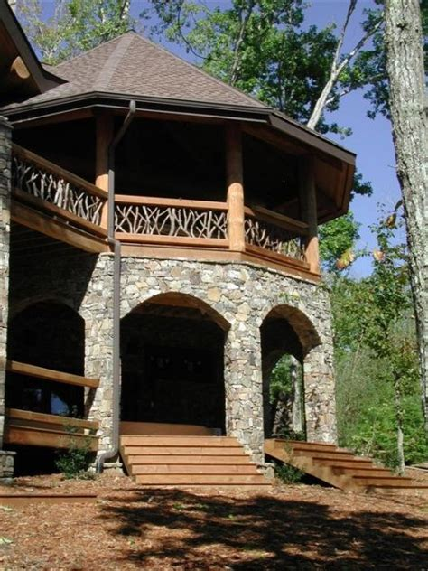 stone turret acts    story attached gazebo featuring twig railing handcrafted chink