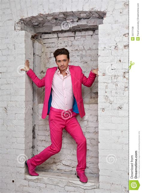 young man  pink suit  shoes stands   wall