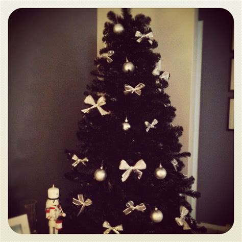 black christmas tree with white and silver bows and
