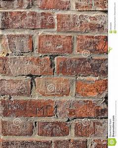 Old Red Wall With Engraved Bricks Stock Photo