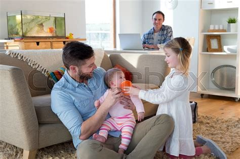 Same Sex Male Couple At Home With Their Two Daughters One