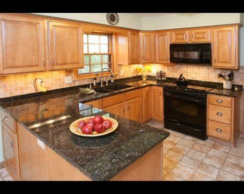 granite countertops light wood cabinets and