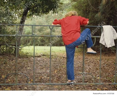 Woman Climbing Fence Photo