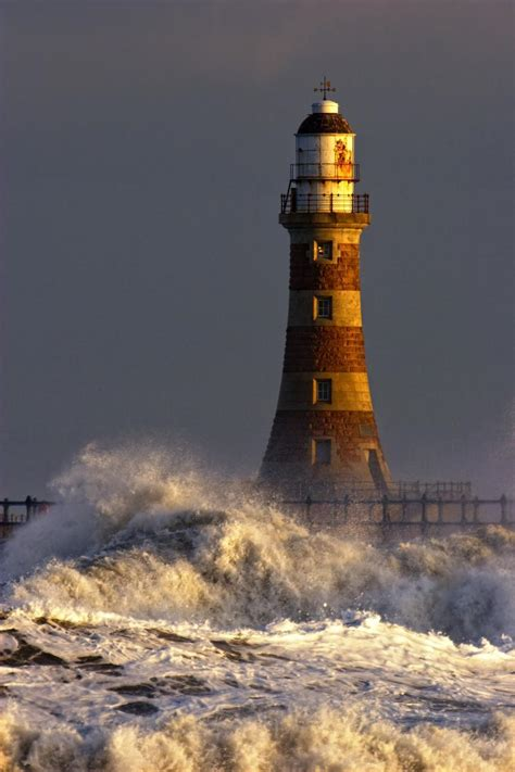 waves crashing against a lighthouse tyne and wear