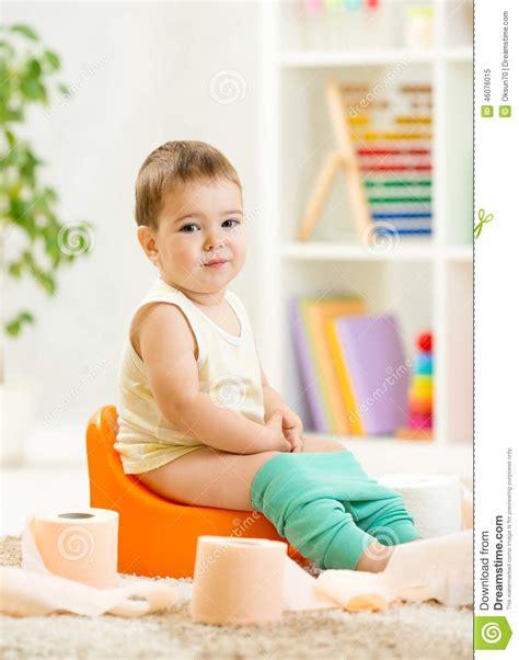 pot de chambre de la enfant de sourire s 39 asseyant sur le pot de chambre avec la