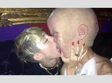 Miley Cyrus locks lips and tongues with man dressed as a