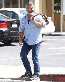Mel Gibson displays his growing biceps as he strides into ...