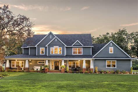 big farm house blue and big rustic modern farmhouse in a green field