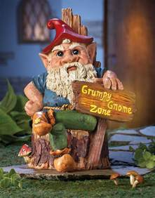 grumpy gnome sitting on tree stump with solar lighted sign